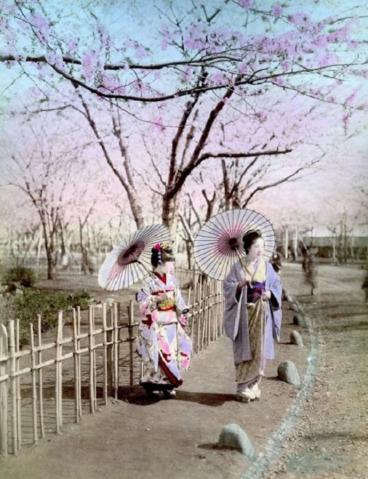 Мама с девочкой в традиционных одеждах прогуливаются улицами города.