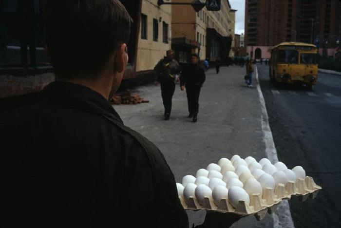 Прохожий с контейнером для транспортировки яиц. СССР, Норильск, 1993 год.