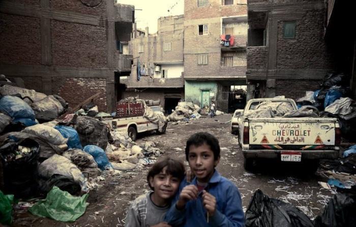 Квартал Каира, заваленный огромными тюками, которые местами уже перекрывают проезд, свешиваются с балконов, лежат на крышах домов и во дворах.