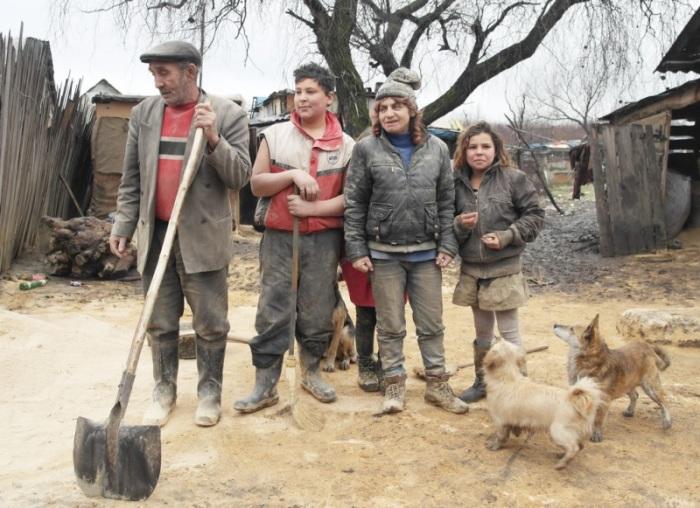 Семья цыган разгребает лопатами опилки, которые они используют для отопления дома.  Автор фото: Максим Беспалов.
