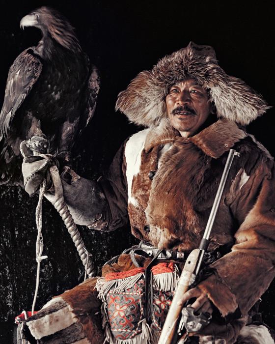 Беркут сидит на руке охотника, на специальной рукавице.
