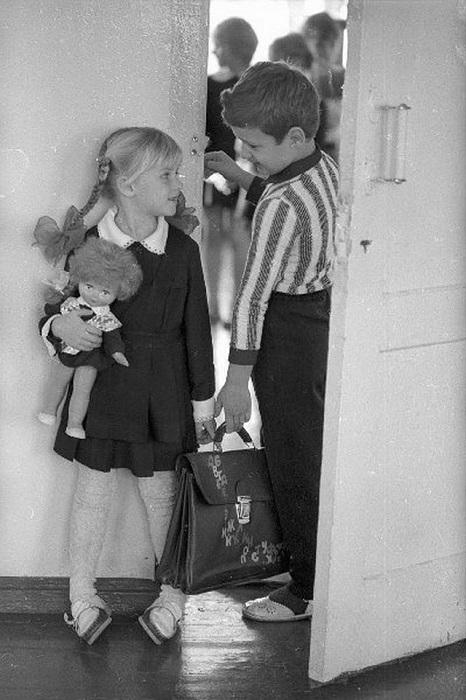 Девочка-первоклассница вместе со своей любимой куклой, которая тоже одета в школьную форму.
