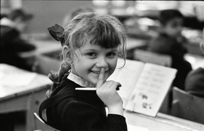 Улыбающаяся девочка-первоклассница позирует фотографу во время урока.
