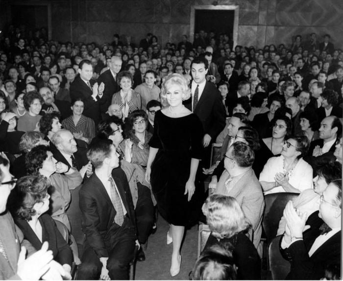 Американская актриса идет между рядами московских зрителей в сопровождении Казакова в 1962 году.