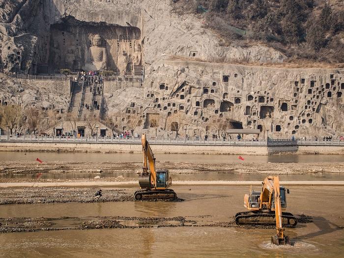 В Китае такое странное соседство – вырезанный в скале древний буддистский храм и совсем рядом экскаваторы проводили земельные работы... Фотограф - Yann H..