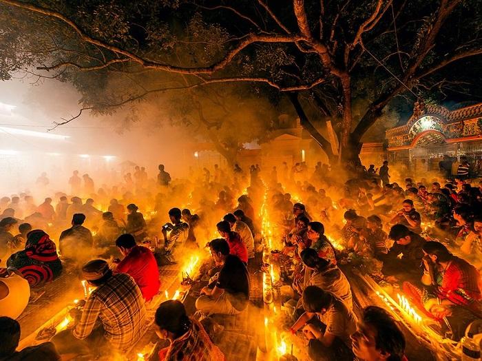 Индуистский фестиваль в Бангладеше, люди зажигают огни и благовония в таком количестве, что становится тяжело дышать от дыма, и это при том, что все индуисты должны в этот период голодать. Фотограф - Syed Hassan.
