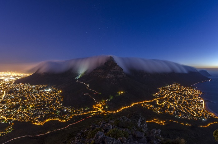 Столовая гора окутана в одеяло из тумана, который медленно сползает на мерцающий в ночи Кейптаун. Фотограф - Brendon Wainwright.