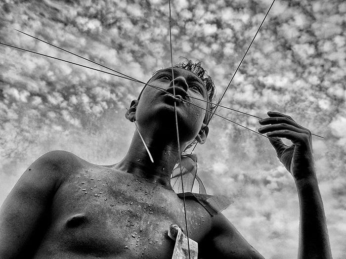 Верующий пронзает свое лицо спицами во время индуистского фестиваля Чарак Пуджа в Западной Бенгалии, Индия. Фотограф - Avishek Das.