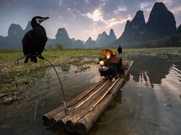Голодного баклана на веревке бросают в воду, тот хватает рыбу, но рыбак забирает добычу прямо из глотки птицы... Фотограф - Abderazak Tissoukai.