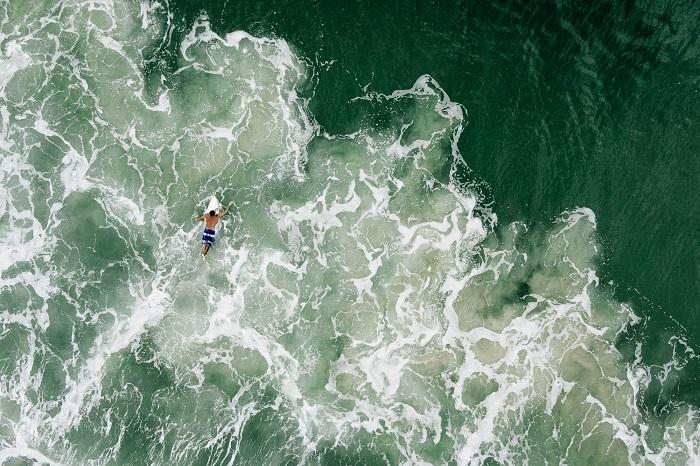 Отчаянный серфингист на красивых морских волнах. Фотограф - Chris Schmid.