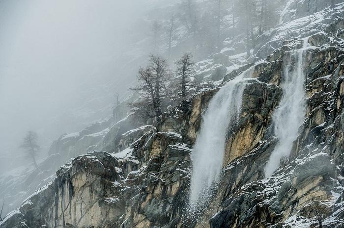 Сухой снег сыпется со скал, создавая впечатление водопада. Фотограф - Stefano Unterthiner.