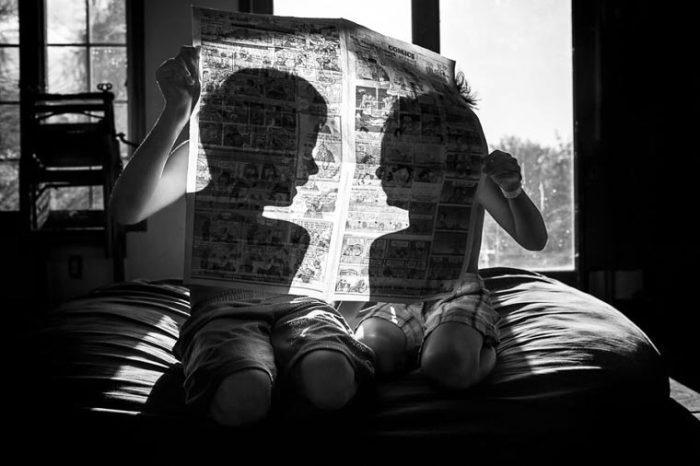 Игра фотографа с тенью детей, читающих комиксы в газете. Фотограф: Эшли Карлтон, США.