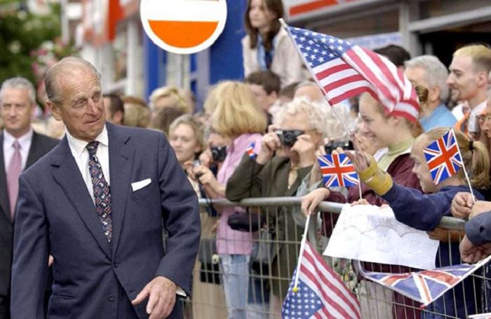 Принц Филипп старается держаться подальше от ребят, размахивающих флажками в Кеттеринге (графство Нортгемптоншир).