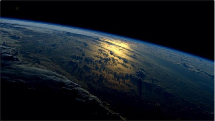 Отблески уходящего солнца на поверхности земли отражаются золотым сиянием.