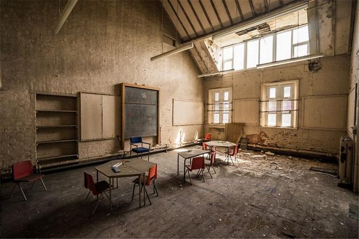 Покрытая слоем пыли грифельная доска соседствует со стоящими рядом столами и стульями в разрушающемся здании в Великобритании.