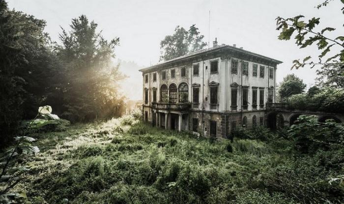 Заброшенный итальянский особняк с давно закрытыми ставнями скрывается среди разросшейся травы и деревьев.