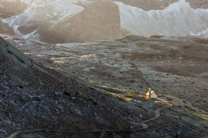 На фоне массивных гор дорога кажется тонкой серпантинной лентой.