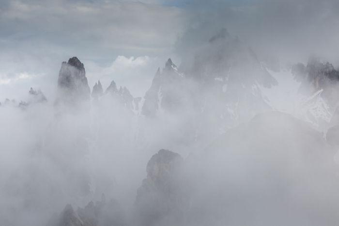 Сквозь густой туман видны только вершины гор.
