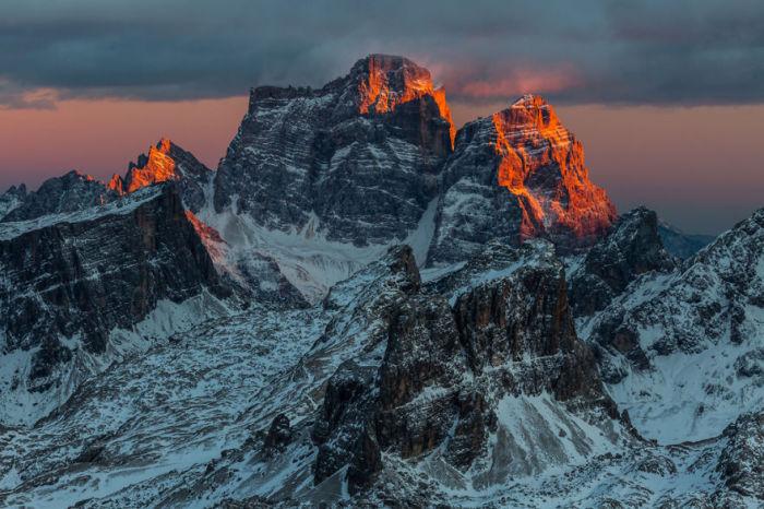 Лучи заходящего солнца скользят по вершинам гор.