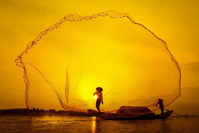 Рыбак закидывает сеть на закате солнца. Фотограф: Туан Нгуйен Манх (Tuan Nguyen Manh).