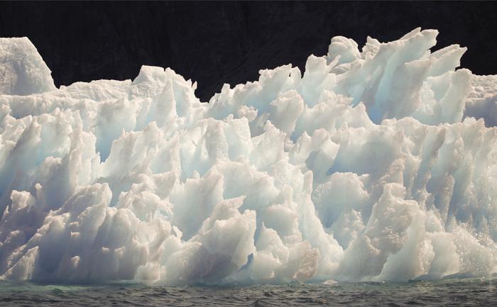 Постепенно разрушающийся айсберг, который плавает в фьорде Эрика на юге Гренландии.