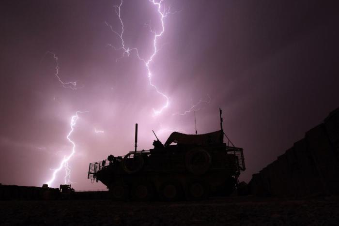 Бронированная машина на фоне молнии во время грозы.