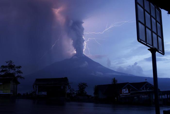 Разряды молнии над извергающимся вулканом Мерапи.
