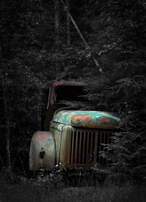 Старая заброшенная машина в чаще густого леса.