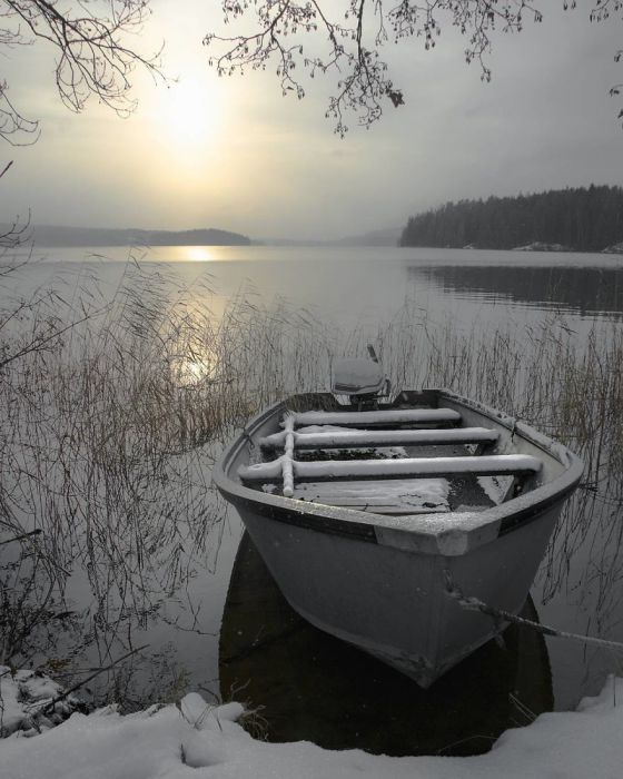 Припорошенная снегом лодка так и манит в дальний путь.