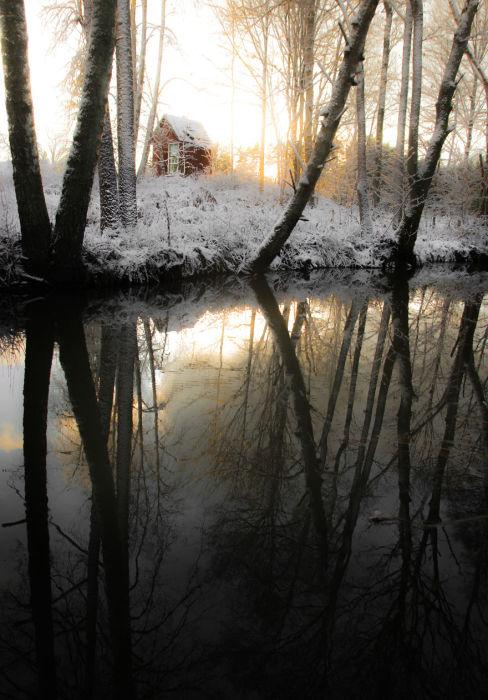 Сказочный домик возле озера укрыт снежным покрывалом.