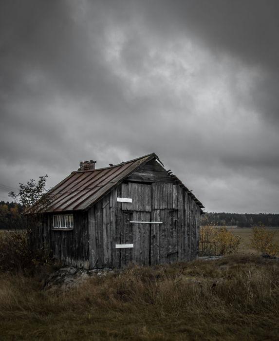 Одинокое деревянное строение посреди поля.