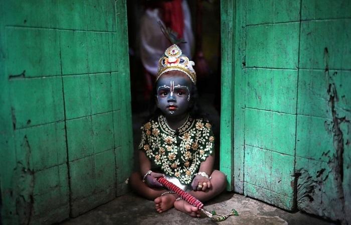 Ребенок в костюме бога Кришны во время праздника Джанмаштами (Город Дакка, Бангладеш).