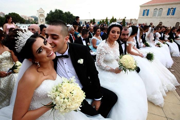 Жених целует невесту во время торжественной церемонии массового бракосочетания в Маронитском Патриархате.