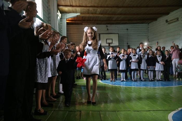 Нарядные школьники деревенской школы на традиционном празднике начала учебного года.