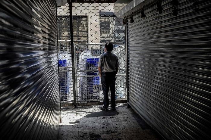Человек стоит у магазина на улице Истикляль, закрытого полицией после побега заключенных.