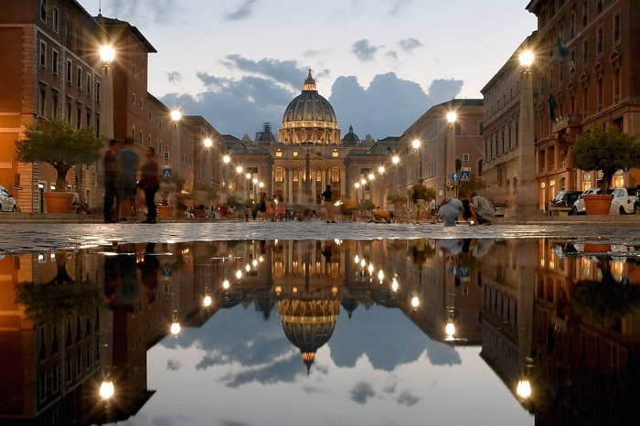 Вечерняя Базилика Святого Петра, отраженная в луже на улице Виа делла Кончилиационе.