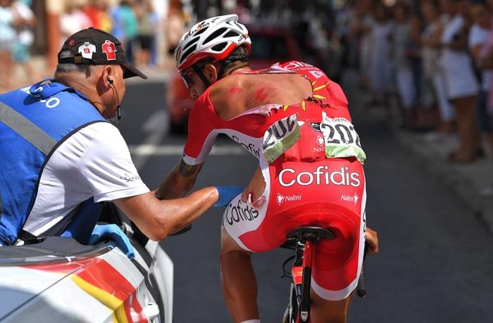Медик осматривает раны французского велосипедиста, полученные после падения во время соревнований.