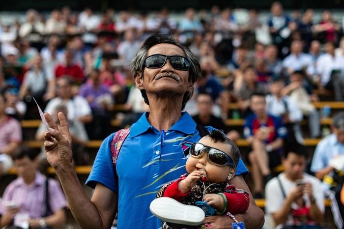 Зритель с куклой на руках ожидает открытия сезона скачек на ипподроме Ша-Тина.