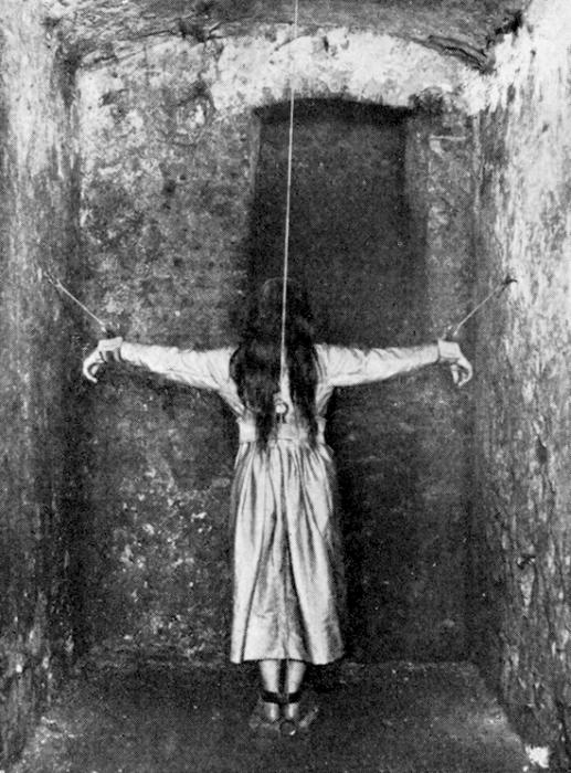 На снимке 1890 года женщина стоит в маленькой камере с привязанными руками, которые закреплены таким образом, чтобы напоминать распятие Христа. Несмотря на очевидную жестокость, подобные методы лечения психических расстройств считались в то время в Германии приемлемыми и допустимыми.