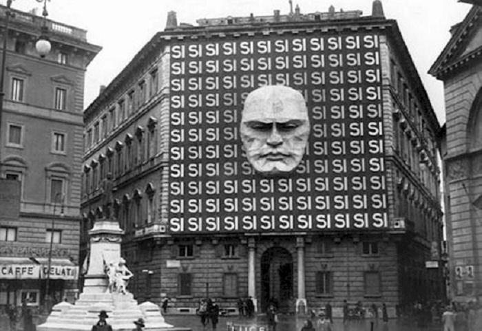 Огромное давящее здание украшено гигантским портретом Бенито Муссолини и многократно повторенным словом Si - «Да».