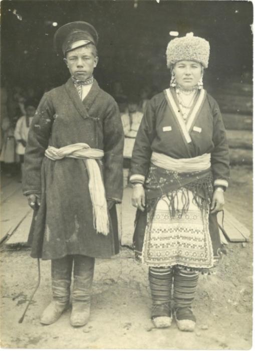 Жених и невеста позируют фотографу в традиционных свадебных костюмах.