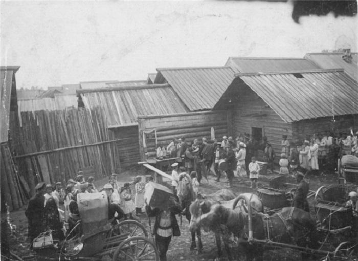 Двор родителей жениха заполнили приглашенные на свадьбу гости и пустующие конные экипажи.