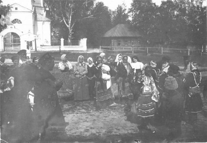 Приглашенные гости, молодожены и простые прохожие собрались на улице во время свадебного торжества.