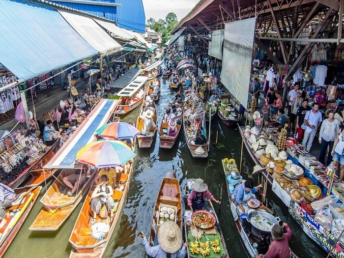 Группа туристов разглядывает товары и совершает покупки на рынке Дамноен Садуак.