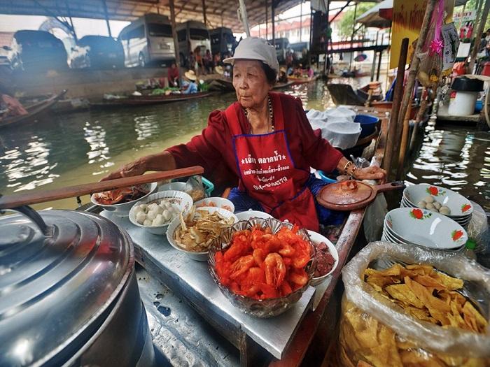 Женщины умело направляют свои лодки на плавающие рынки Таиланда.