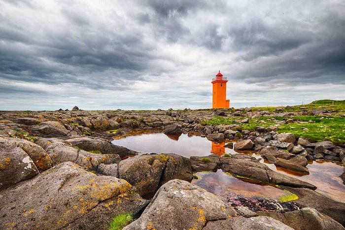 Красивый, оранжевый маяк высотой в одиннадцать с половиной метров стоит на полуострове Рейкьянес.