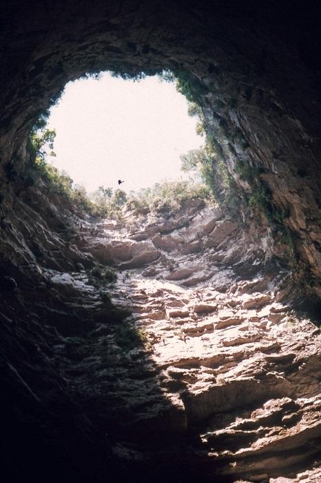 По форме пещера представляет собой расширяющийся вниз карстовый провал, через него по утрам вылетают стаи черных стрижей, за которыми приезжают понаблюдать туристы.