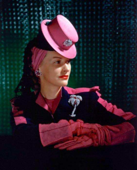 Модель в маленькой ярко-розовой шляпке с брошкой, сочетающейся с перчатками и вставками на костюме.