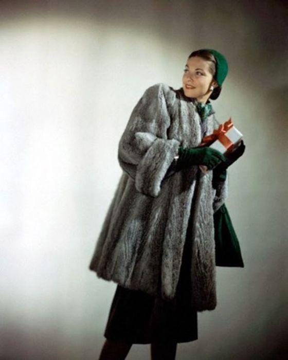 Модель позирует в короткой серой шубе, сочетающейся с аксессуарами насыщенного темно-зеленого цвета.