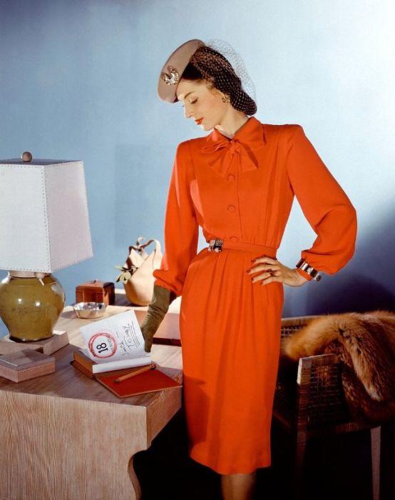 Модель в ярко-оранжевом платье с поясом и воротником-бантом, берет с сеточкой вместе с перчатками того же цвета дополняют образ.